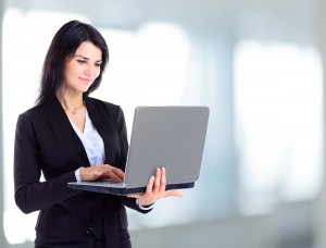 Businesswoman working at a laptop full length